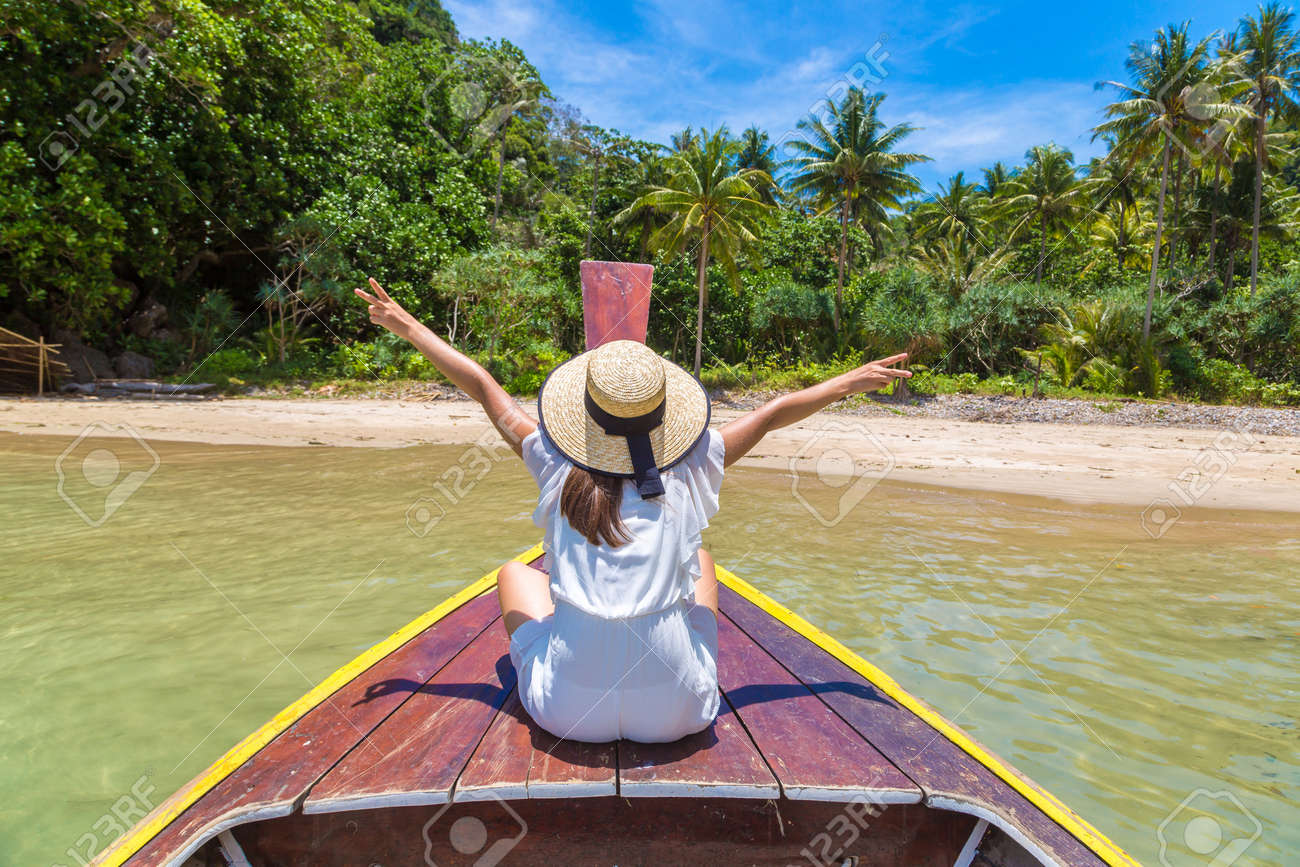 Happy traveler woman relaxing on boat near tropical island in Thailand - 173329238