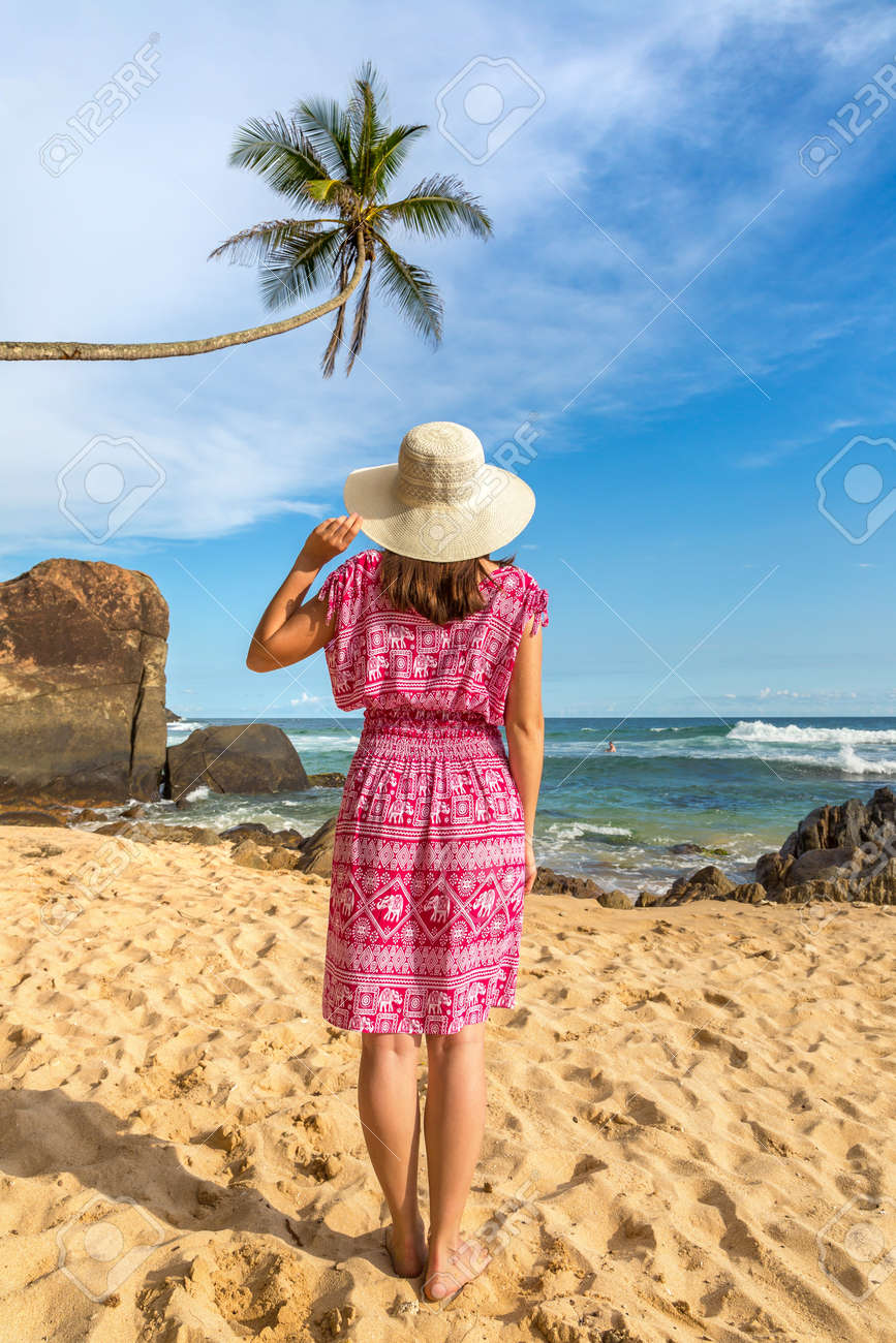 Portriat of young beautiful woman wearing a hat and red dress staying on a tropical beach near sea - 173329245