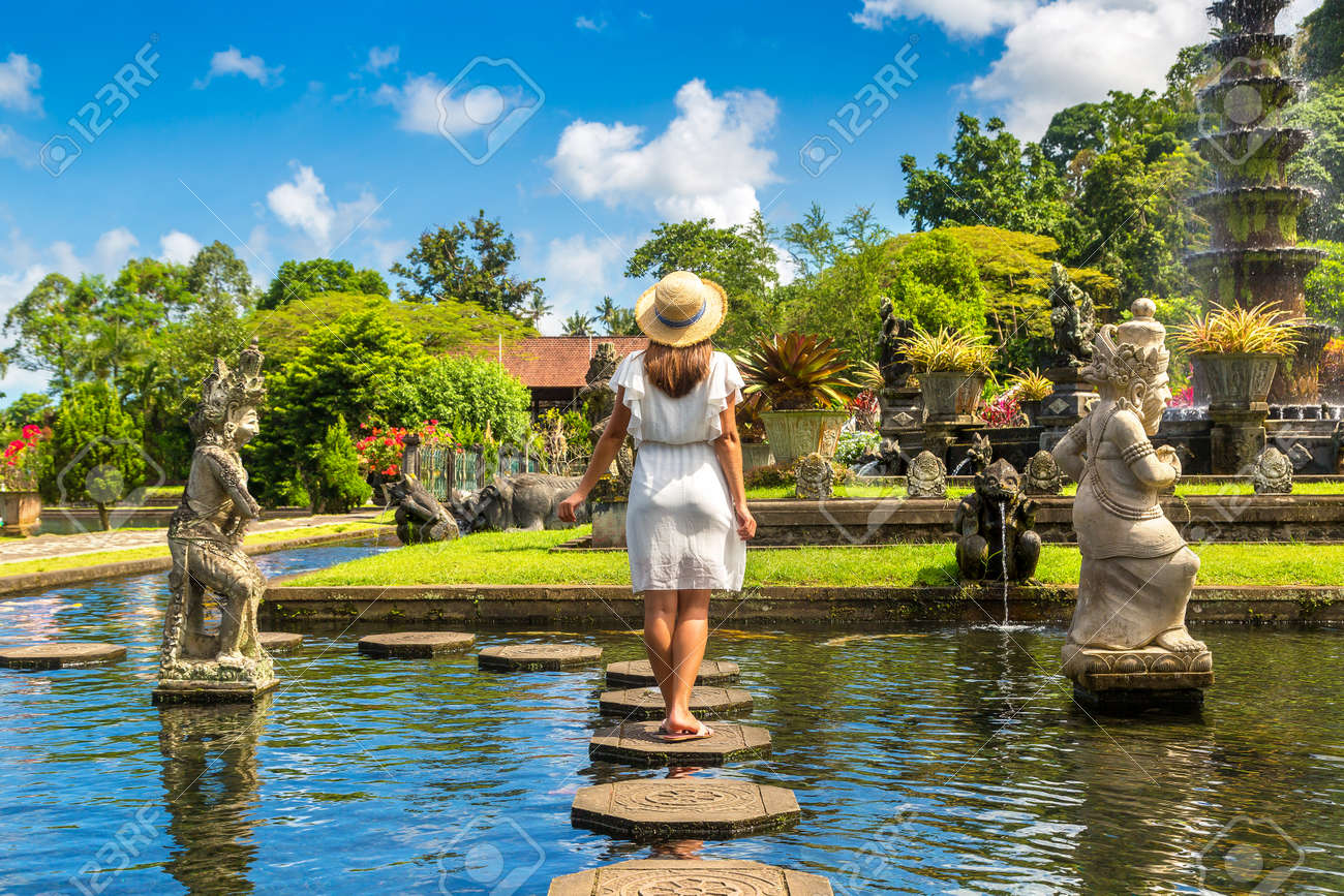 Woman traveler wearing white dress and straw hat at Taman Tirtagangga temple on Bali, Indonesia in a sunny day - 173329254