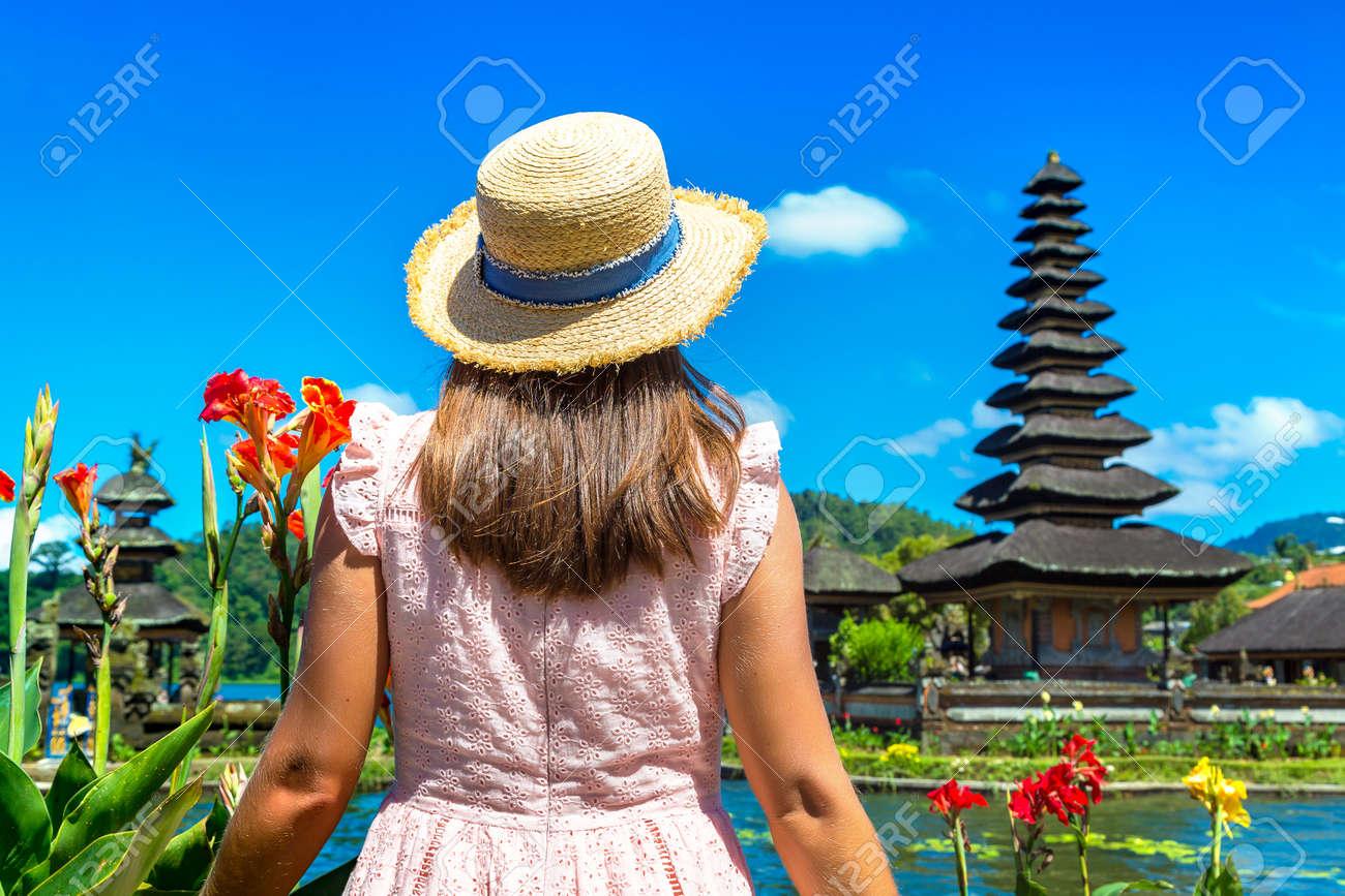 Woman traveler at Pura Ulun Danu Beratan Bedugul temple on a lake in Bali, Indonesia - 173329319