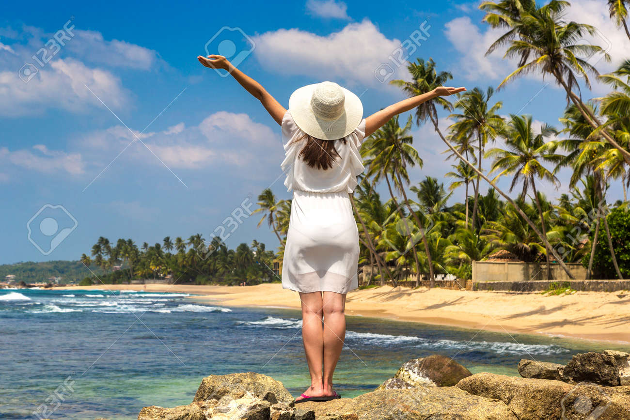 Portriat of young beautiful woman raised hands and wearing a hat and white dress staying on a tropical beach near sea - 173329350
