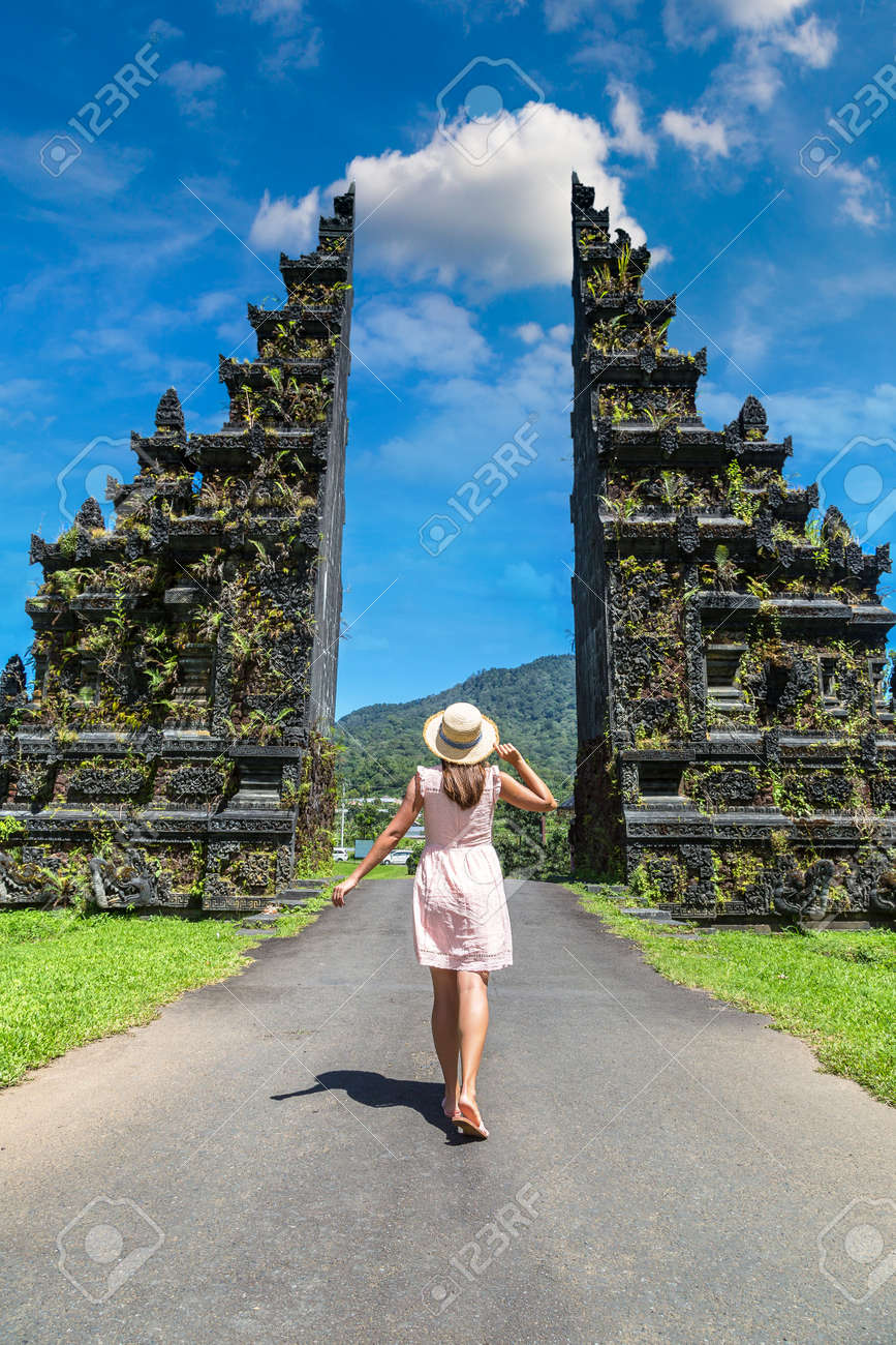 Woman traveler at Bali Handara Gate in Bali, Indonesia in a sunny day - 173329414