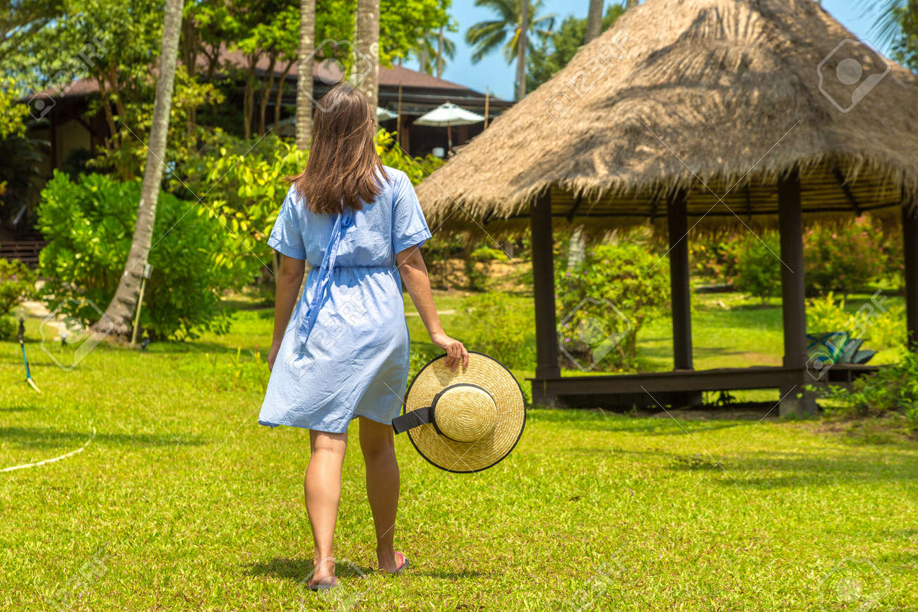 Woman traveler at Gazebo at Luxury tropical resort in a sunny day - 173329423
