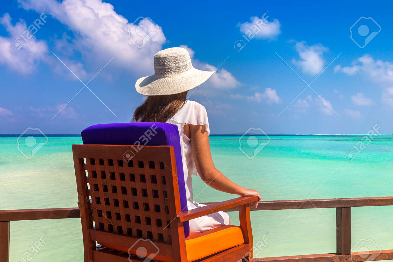 Beautiful woman relaxing in sunbed at luxury tropical beach in a sunny summer day - 173329449