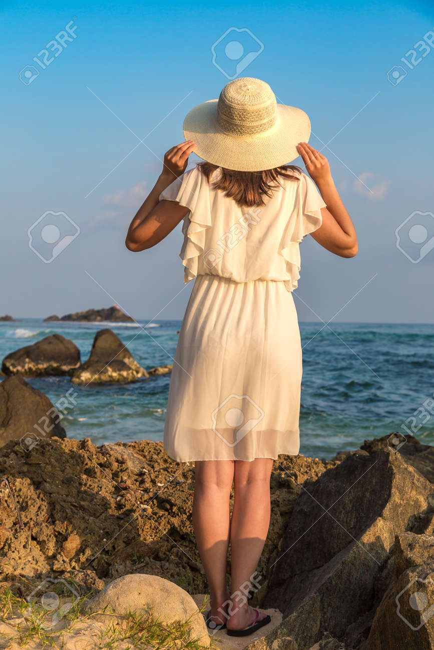 Portriat of young beautiful woman wearing a hat and white dress staying on a tropical beach near sea - 173329456