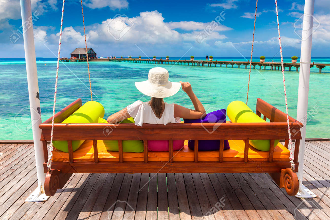 Beautiful woman is sitting on swing at luxury tropical beach in a sunny summer day - 173329510