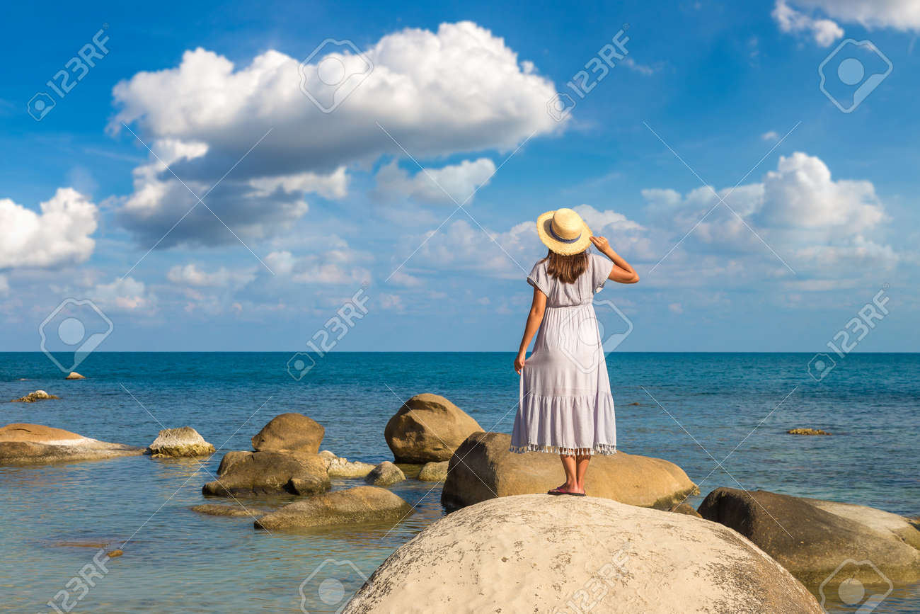 Woman traveler wearing blue dress and straw hat at Silver Beach on Koh Samui island, Thailand in a summer day - 173329537
