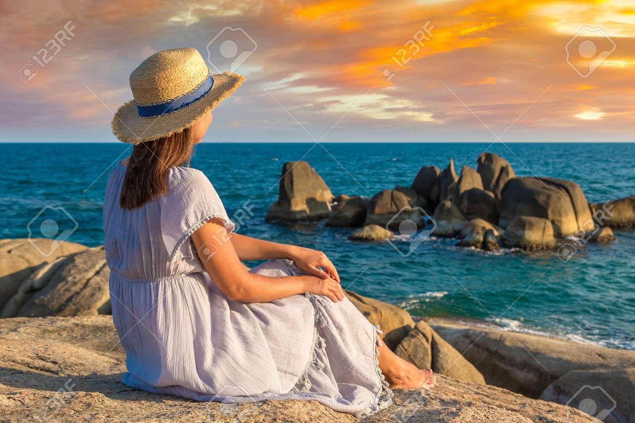 Woman traveler wearing blue dress and straw hat at Hin Ta and Hin Yai Rocks at Samui beach, Thailand in a summy day - 173329829