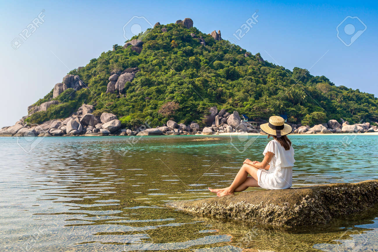 Woman traveler wearing white dress and straw hat at Nang Yuan Island, Koh Tao, Thailand in a summer day - 173329976