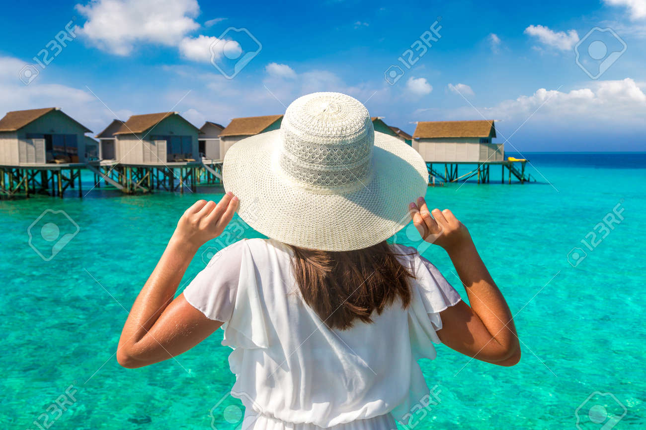 Beautiful young woman in front of water luxury villas standing on the tropical beach jetty (wooden pier) in Maldives island - 173330017