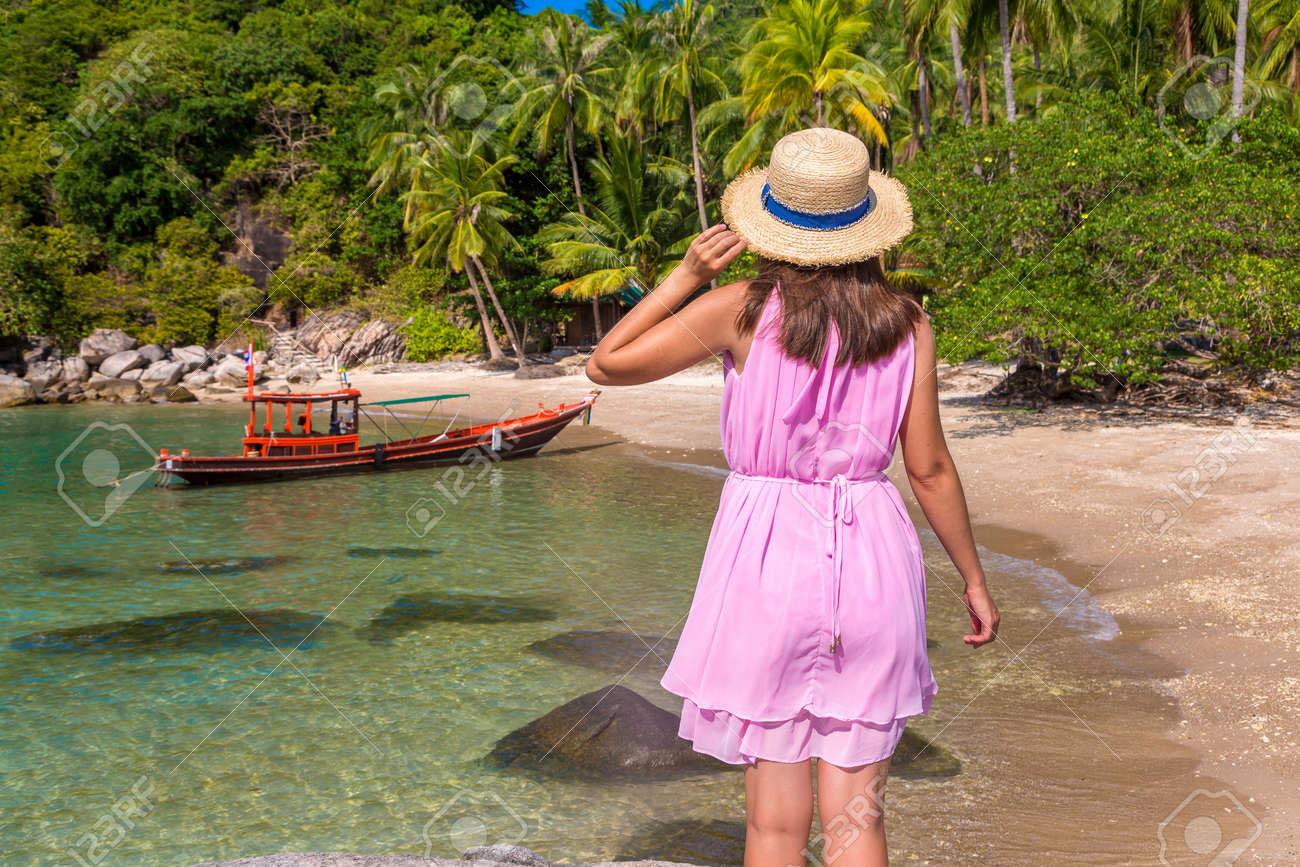 Woman traveler wearing pink dress and straw hat at tropical beach - 173330196