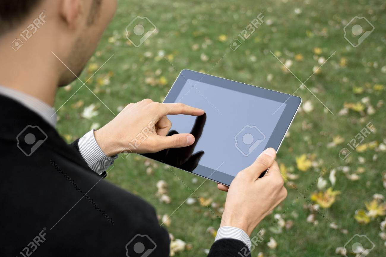 Businessman outdoors working with touch screen device. Stock Photo - 11225116