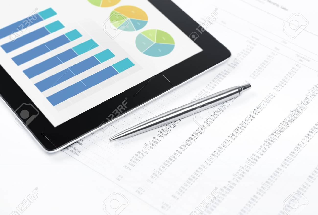 Modern workplace with digital tablet showing charts and diagram on screen, pen and paper with numbers Stock Photo - 13430053