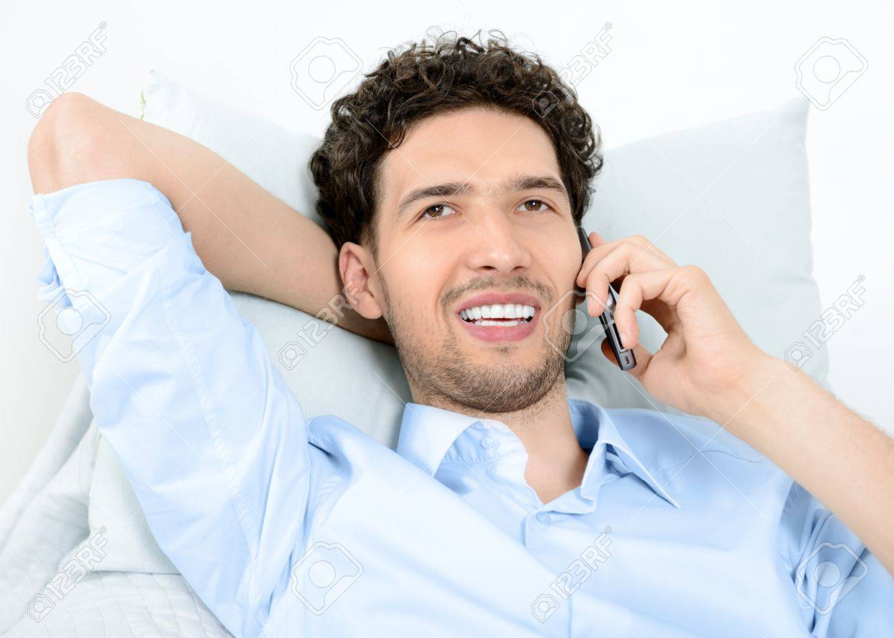 Young handsome man talking on modern mobile phone  Studio shot Stock Photo - 14937275