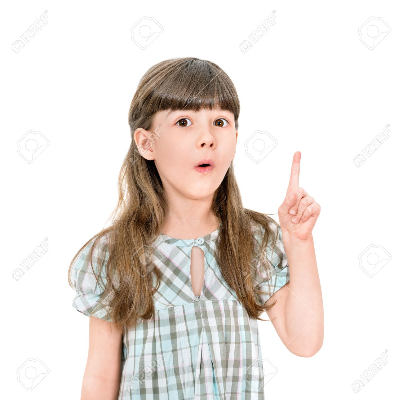 Clever little girl with a bright idea pointing upwards with her finger to gain attention  Isolated on white with blank copyspace above her finger Stock Photo - 18459815