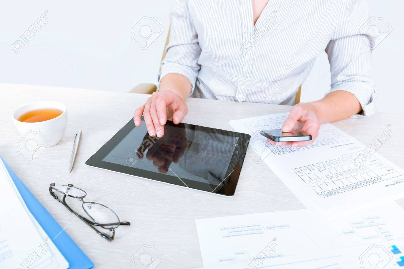Successful businesswoman sitting at desk and simultaneously using modern devices for business communication and analyzing sales statistics for the month period of time Stock Photo - 19483051
