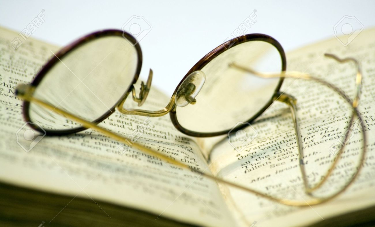 A close-up of a old open book with a pair of antique glasses on it. - 745338