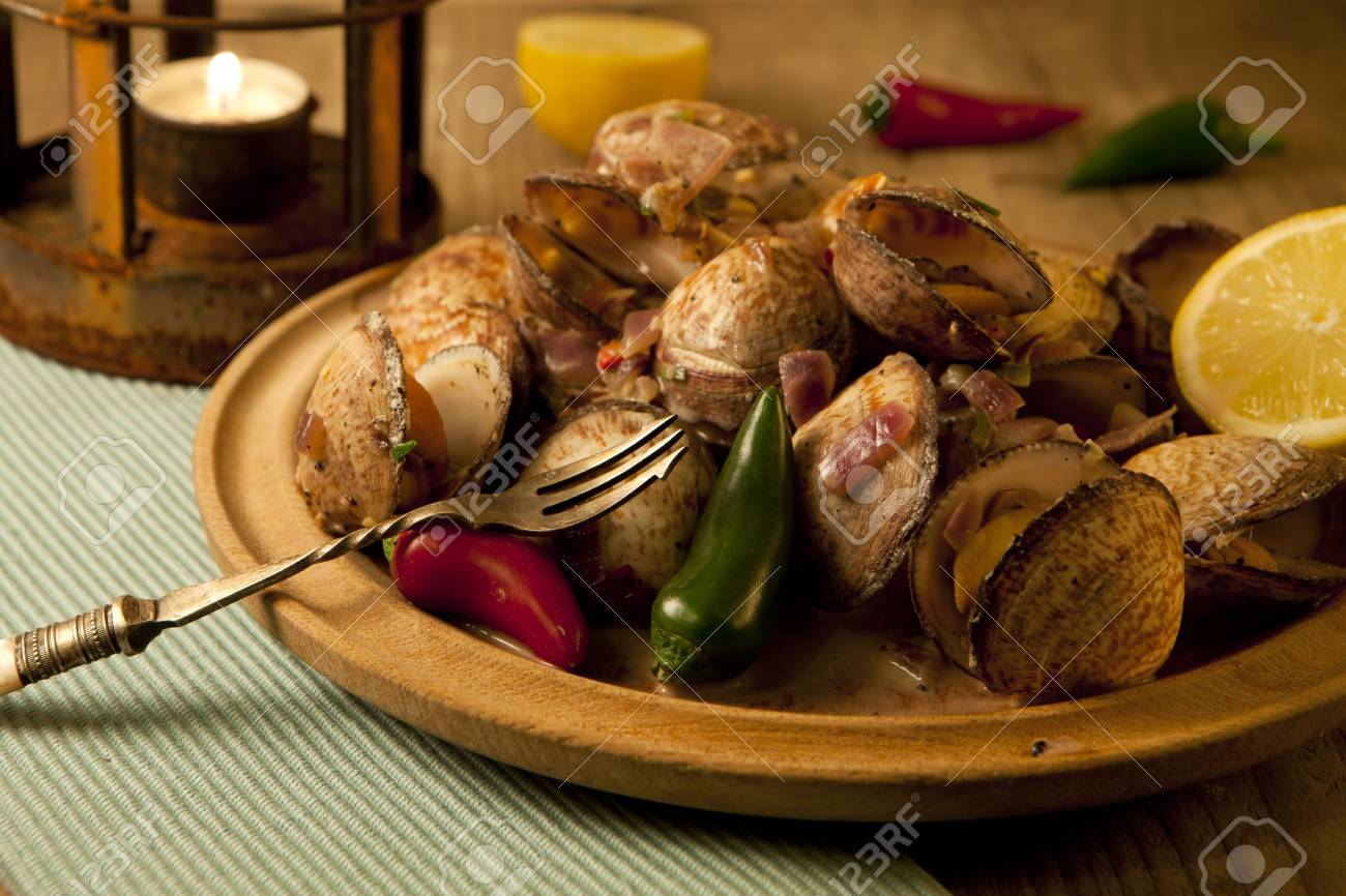 Chili flavoured clams on a wooden plate ready for eating. Stock Photo - 9244158