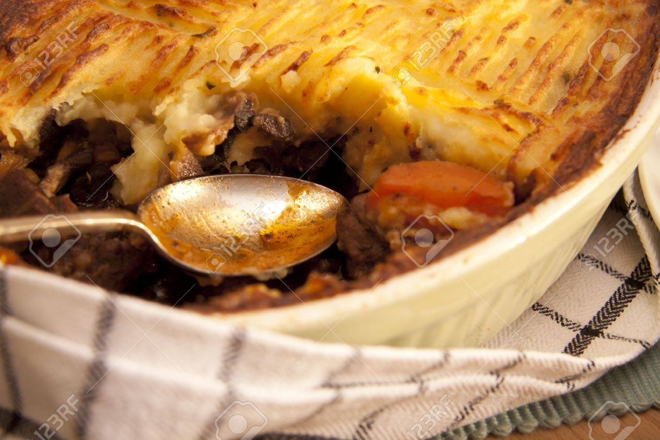 A delicious home made meat pie on a wooden table that makes your mouth water. - 9660292