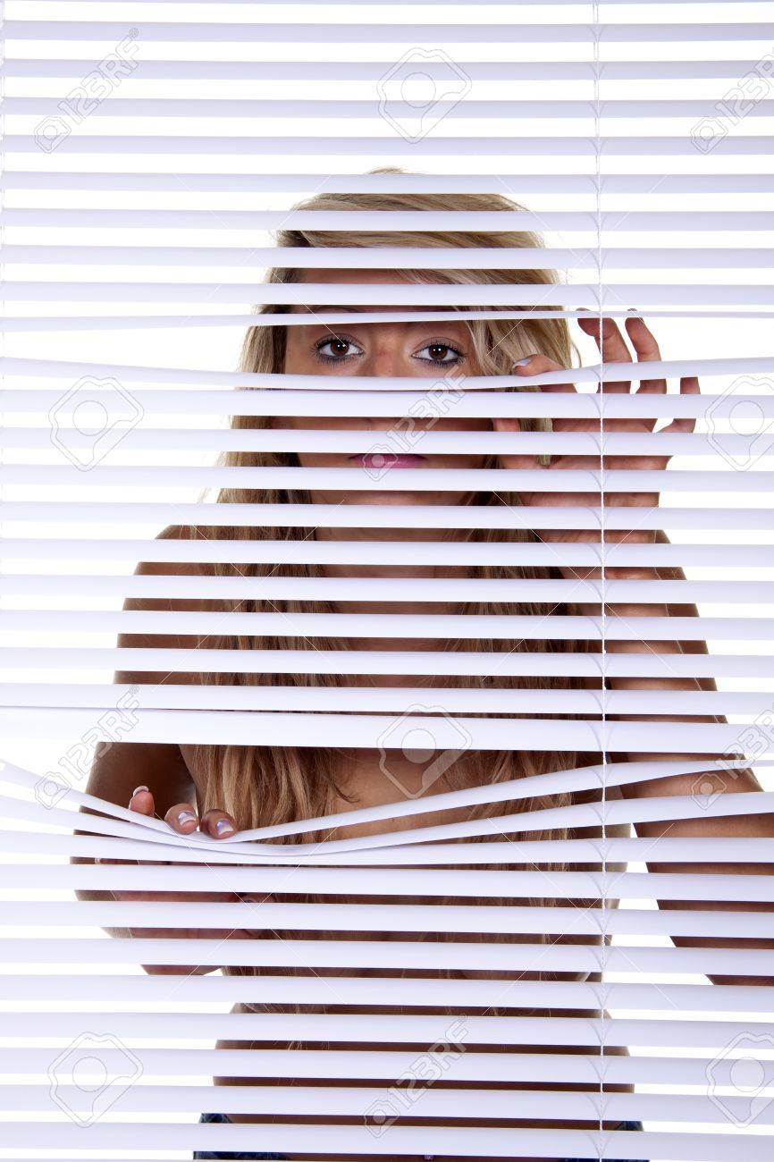 A young blond woman looking trough venison blinds. Stock Photo - 10267848