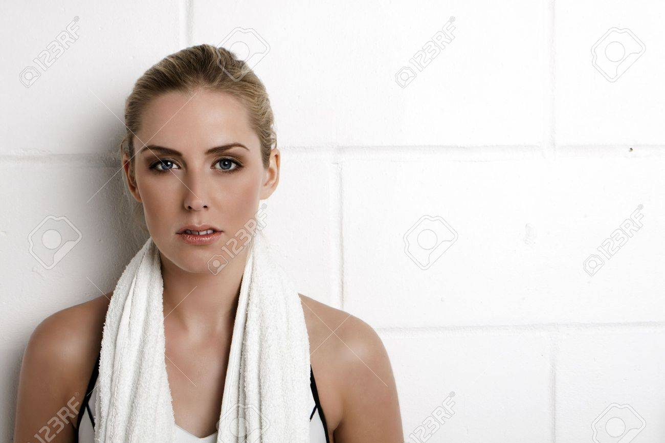 Beautiful blond woman standing against a wall in a gym with a towel around her neck. - 11287257