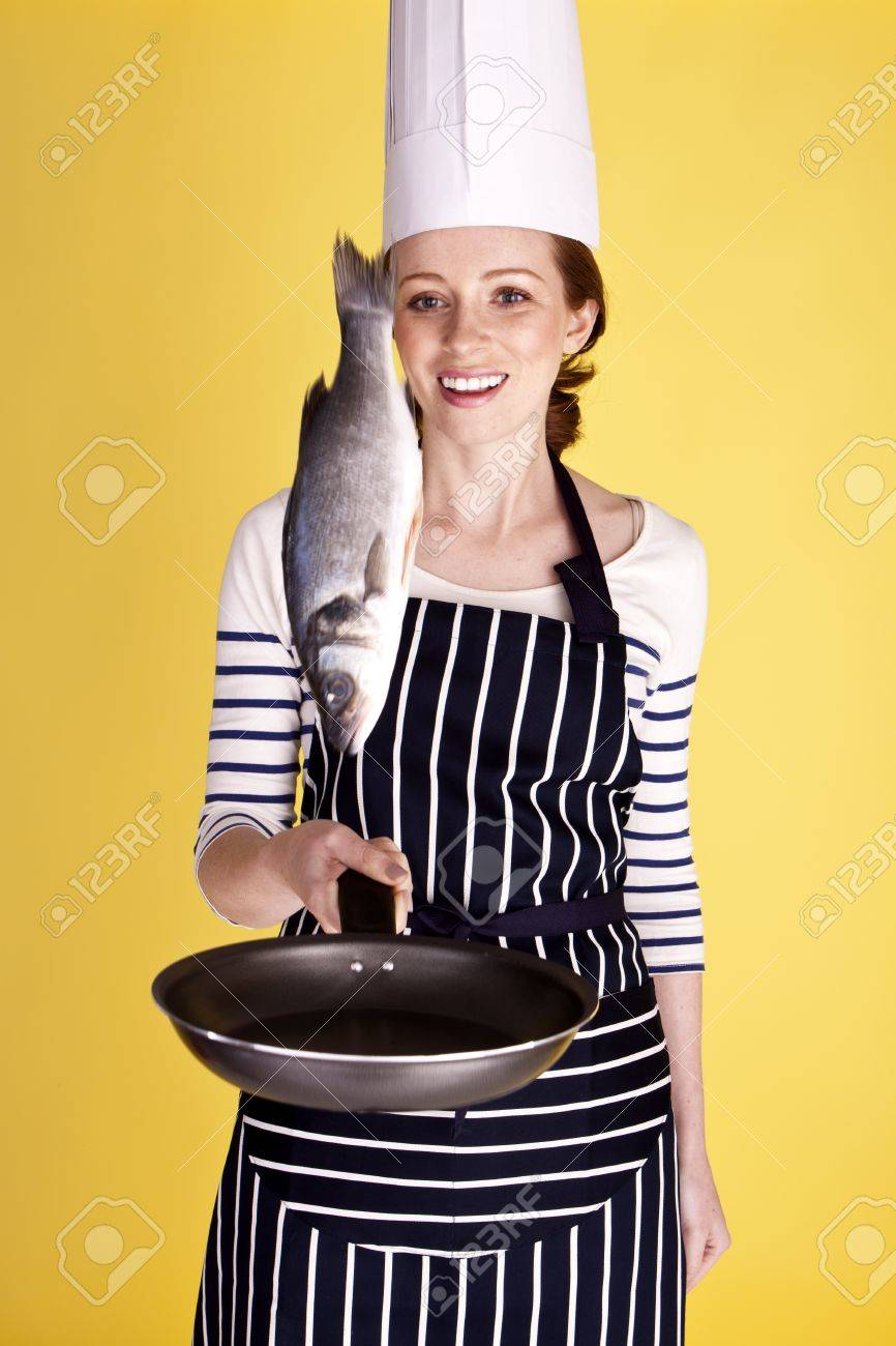 A young attractive female chef flipping a fish in a pan. Stock Photo - 12100534