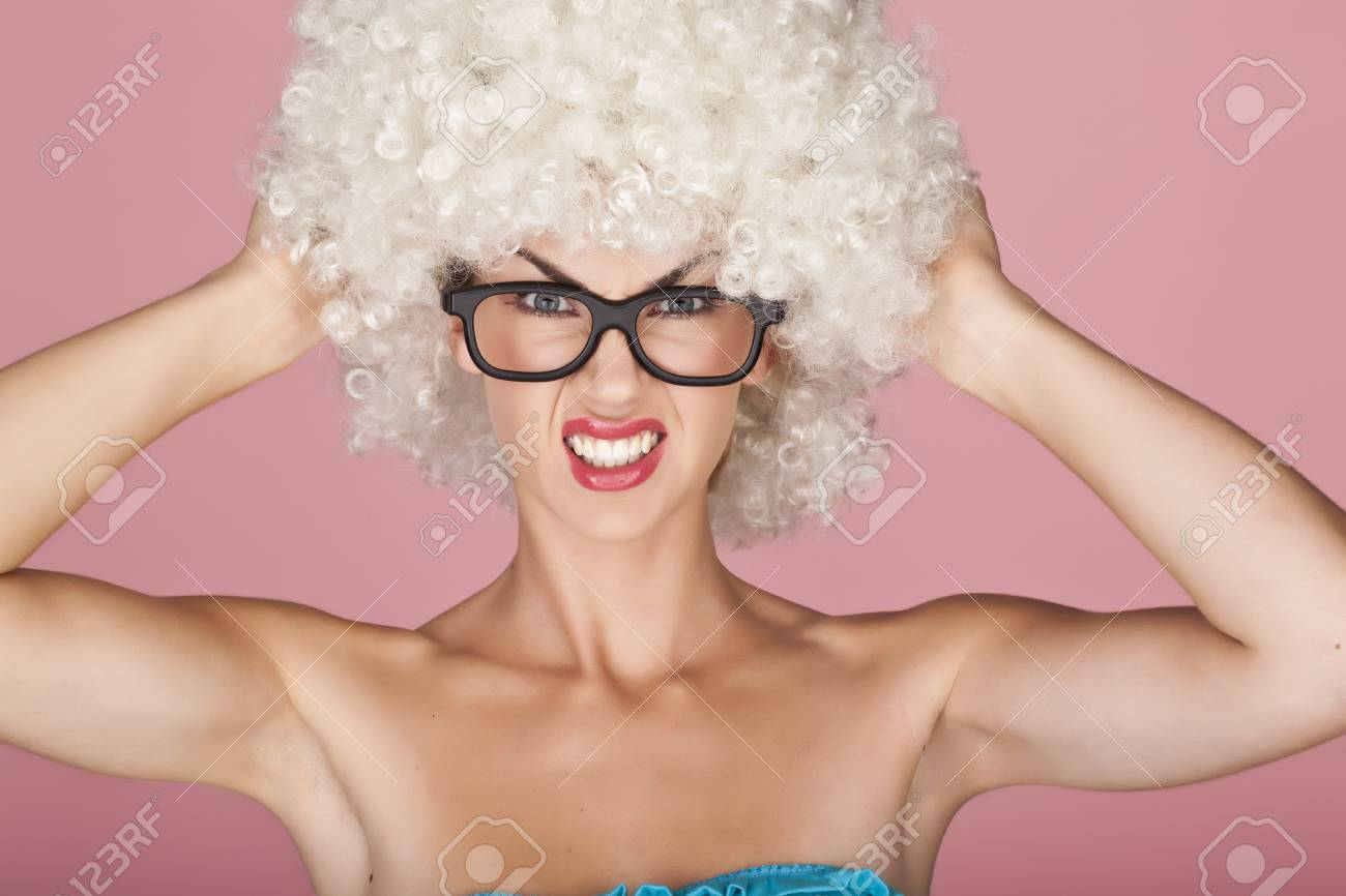 Playful and funny woman wearing a curly wig on a pink background Stock Photo - 15758083