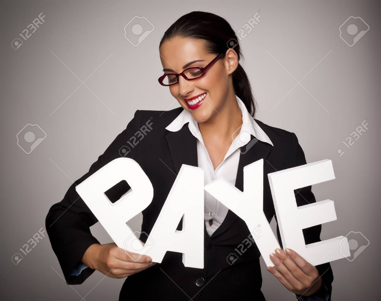 Income tax concept with a beautiful businesswoman holding letters spelling out PAYE that stands for pay as you earn - 16249963