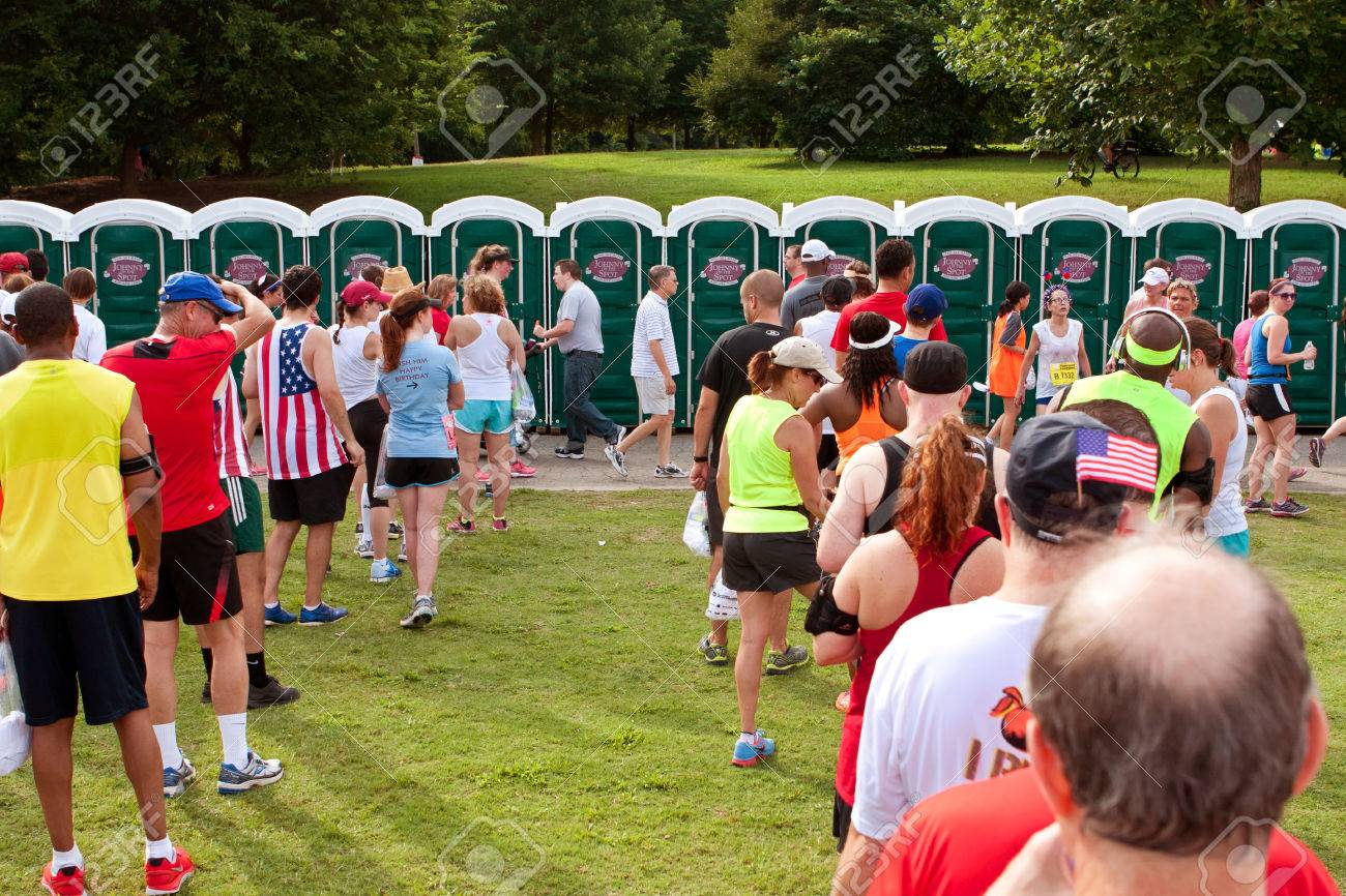 Atlanta, GA, USA - July 4, 2014: Exhausted runners wait in long lines to use a Johnny On The Spot portable toilet, after just completing the Peachtree Road Race 10K. - 31550391