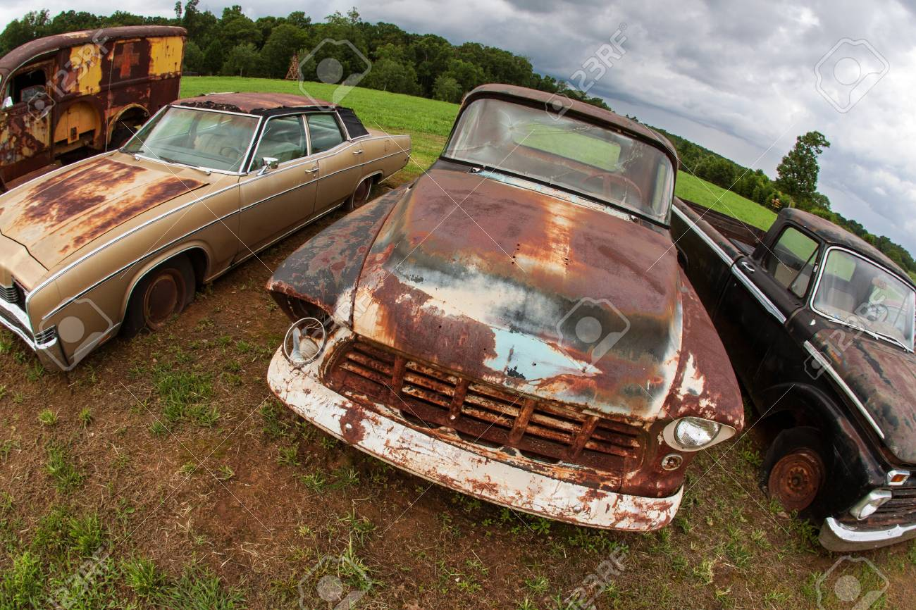 Rusted Antique Vehicles Sit Lined Up In An Auto Junkyard Stock Photo ...