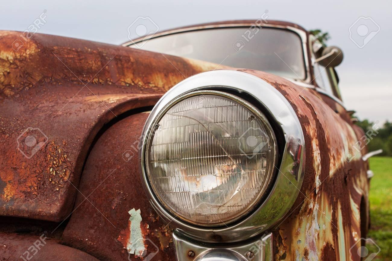 Cracked headlight on old rusted junkyard car - 88501622