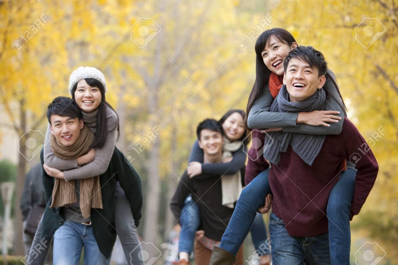 Estudiantes Universitarios En Parejas Jugando A Cuestas Al Aire