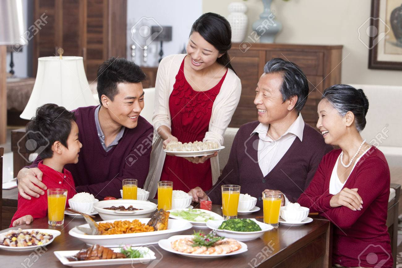 merry family having chinese new year dinner stock photo 74923579 - Chinese New Year Dinner