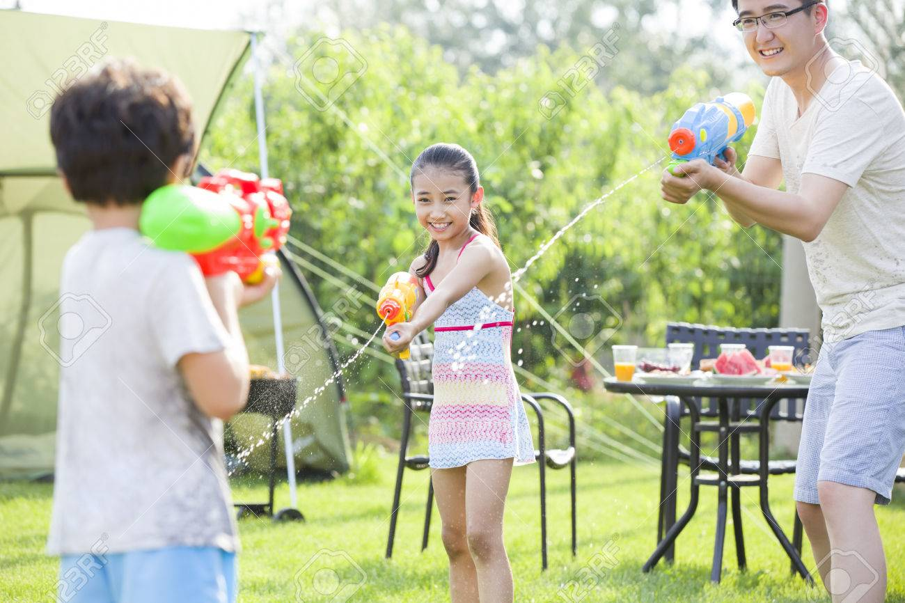 Happy father and children playing squirt guns Stock Photo - 75030653