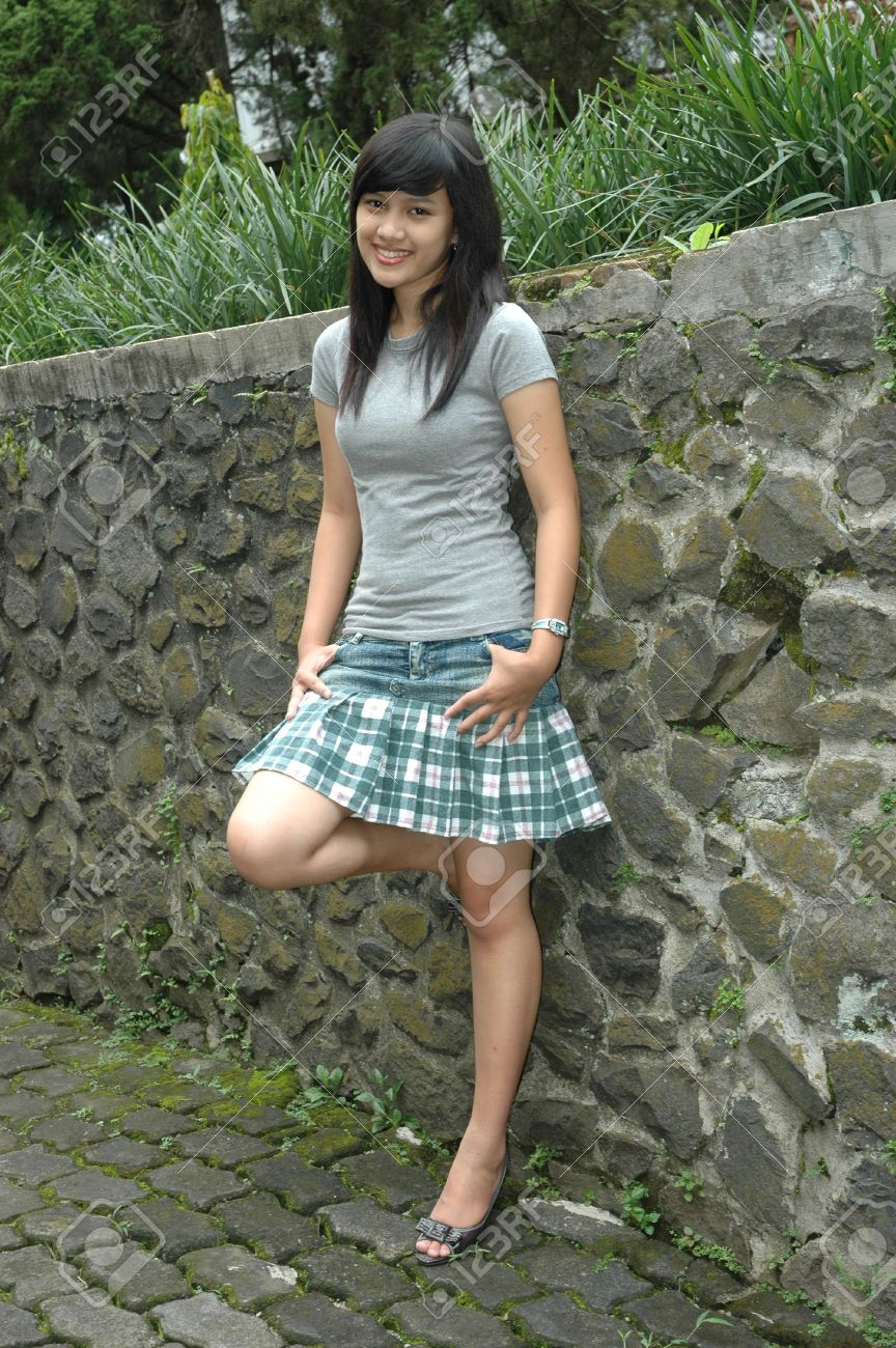 young lady stand up beside rock wall stock photo picture and