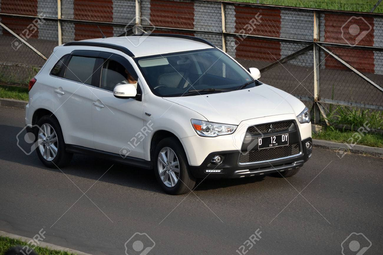 stock photo bandung indonesia june 16 2014 white colored mitsubishi outlander sport cruising on the road