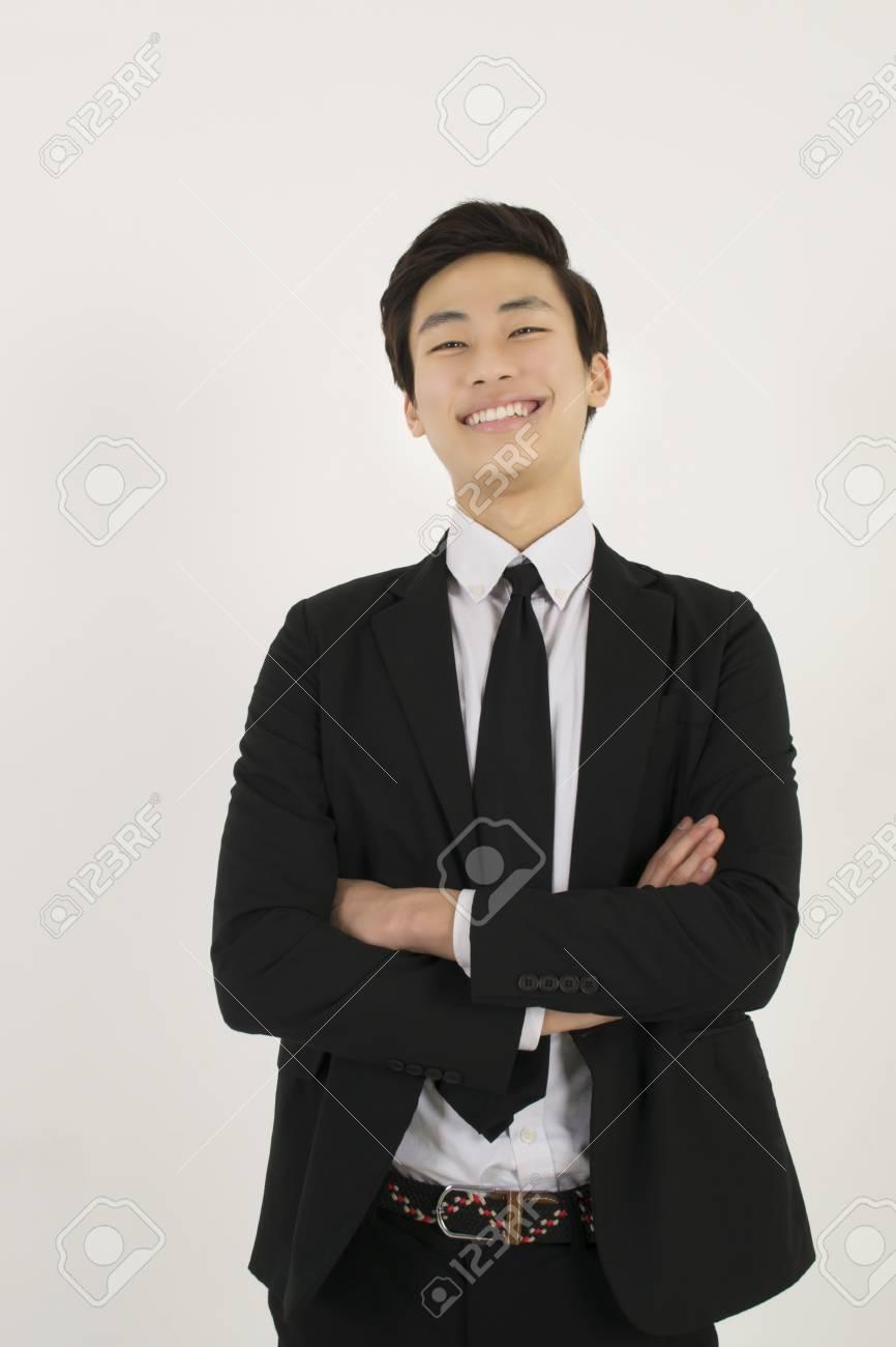 80ff629ba0c32 Foto de archivo - Hombre joven asiático en un traje negro con los brazos  cruzados