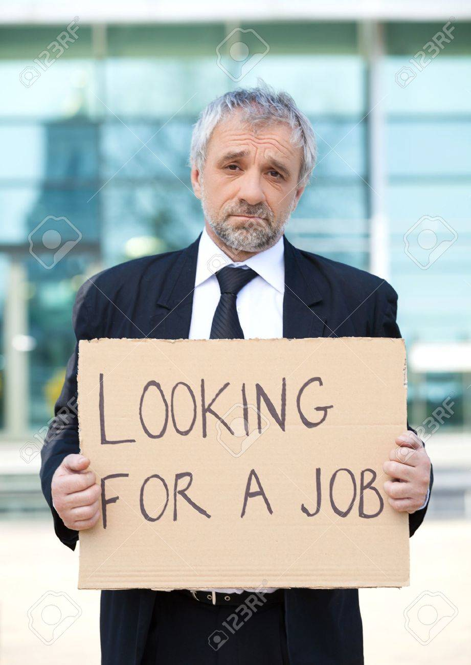 looking for a job depressed senior man in formalwear holding looking for a job depressed senior man in formalwear holding a poster stock photo