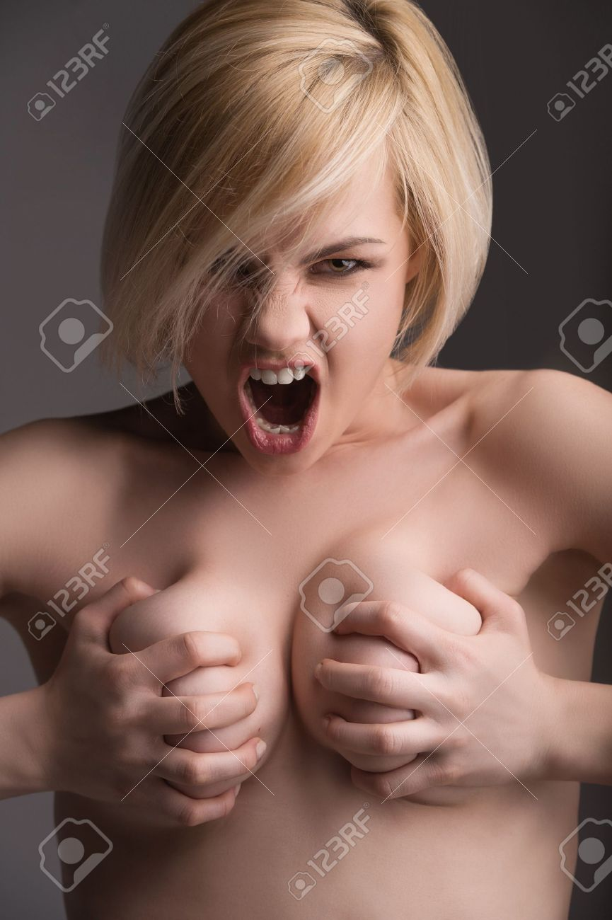 naked emotions. beautiful young woman holding her breast in hands