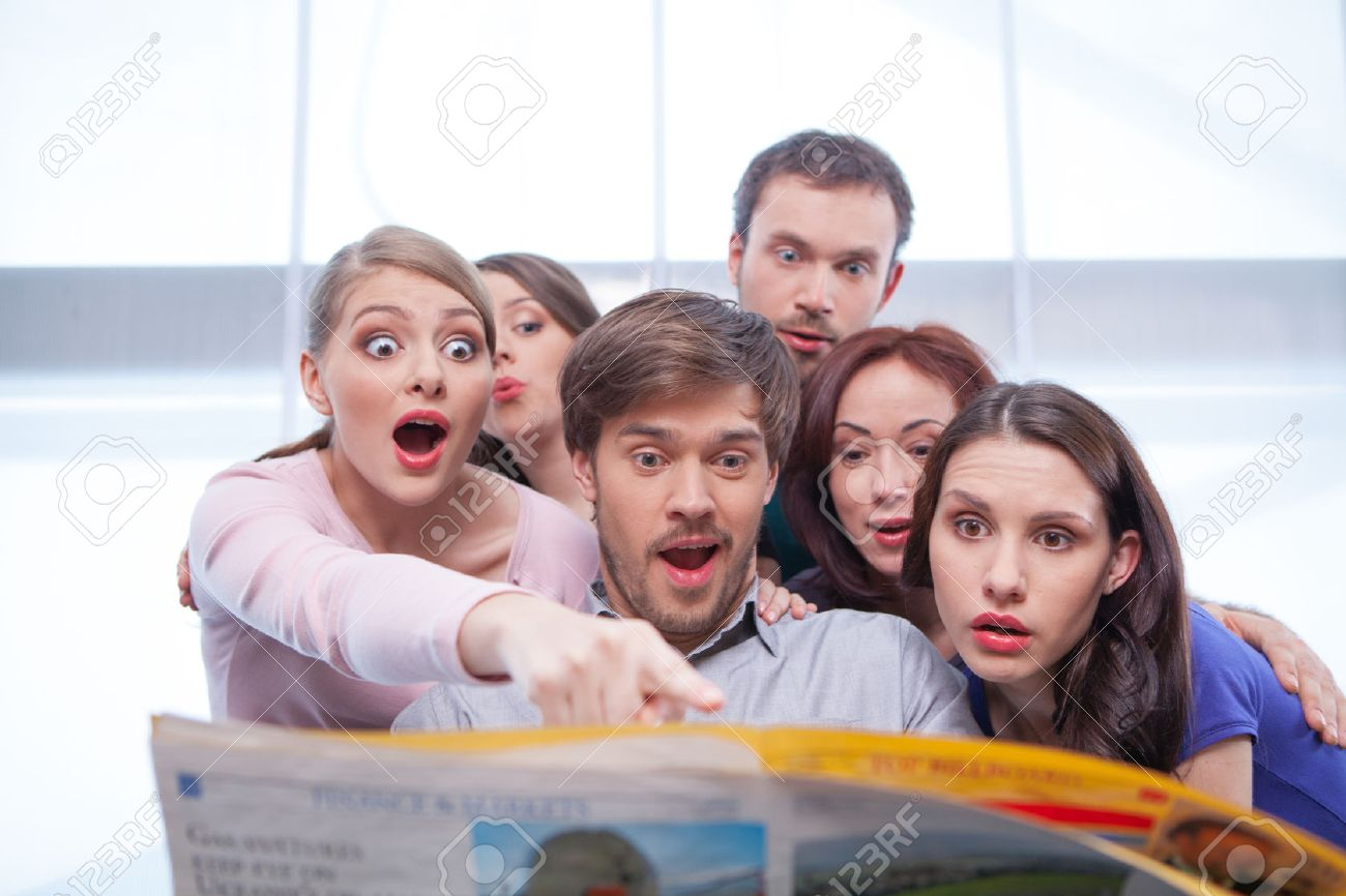 group of young people reading newspaper. looking very surprised