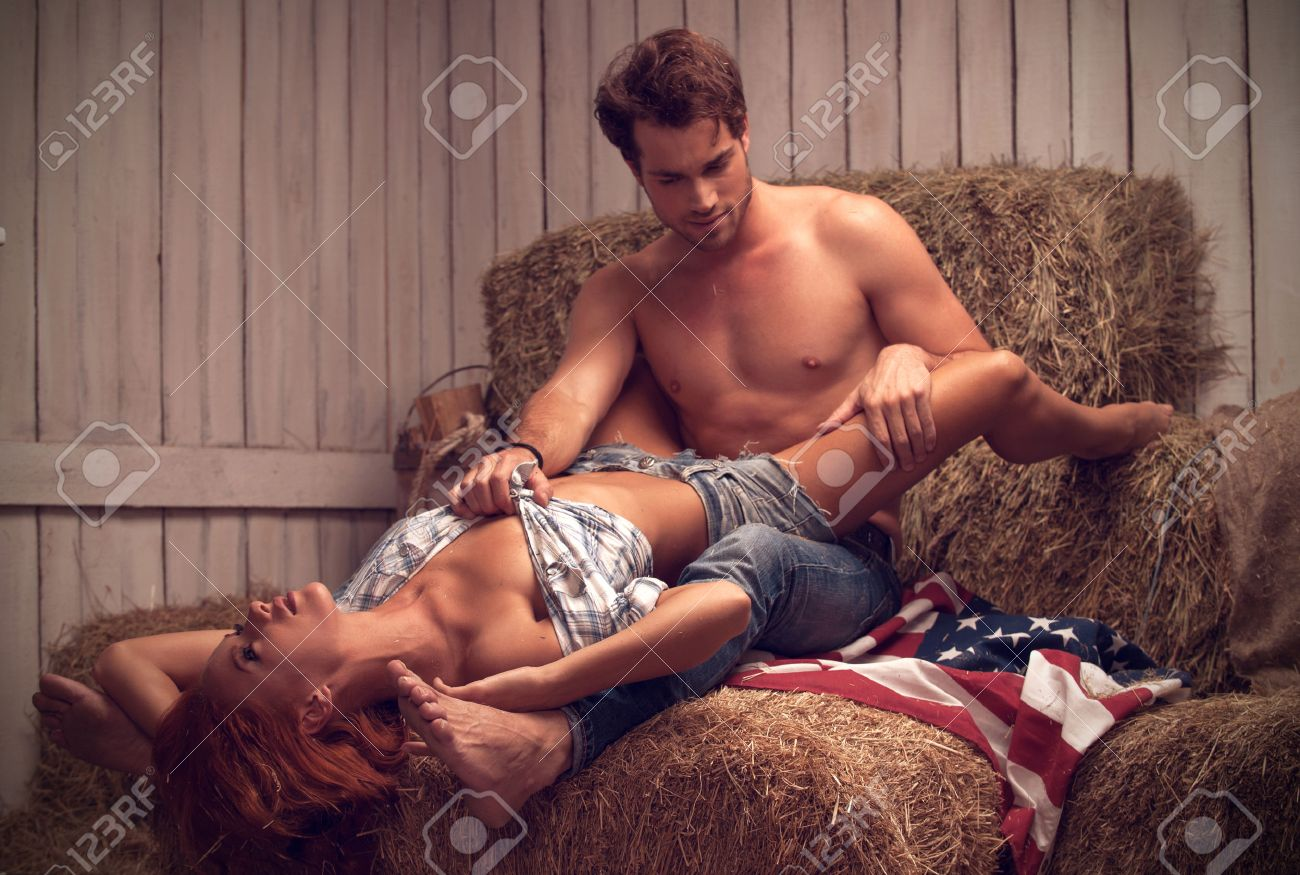 sexy couple having sex in hayloft. sexy man with nude torso stock