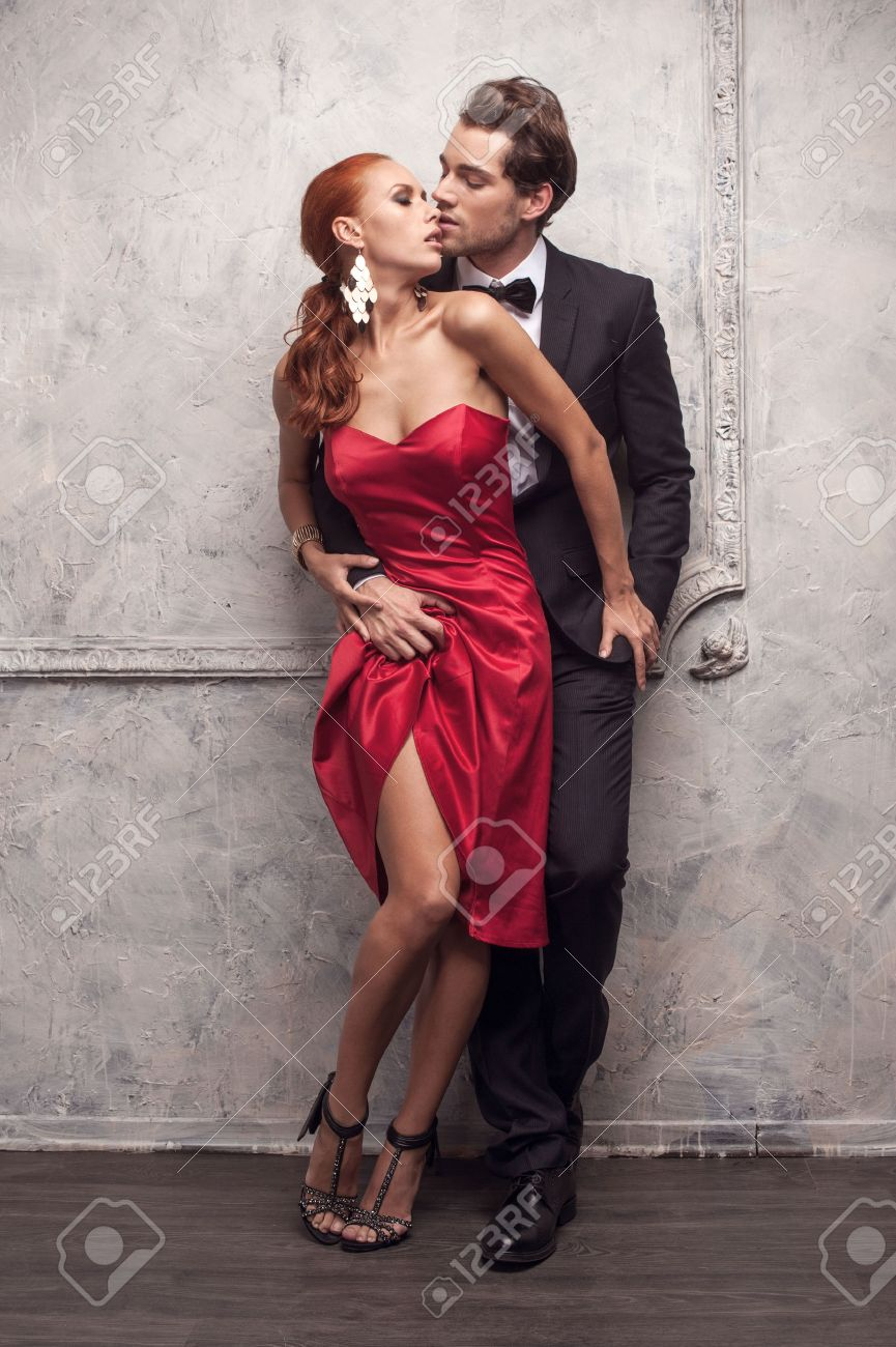 Beautiful couple in classical outfits. Standing and kissing with passion Stock Photo - 22984905