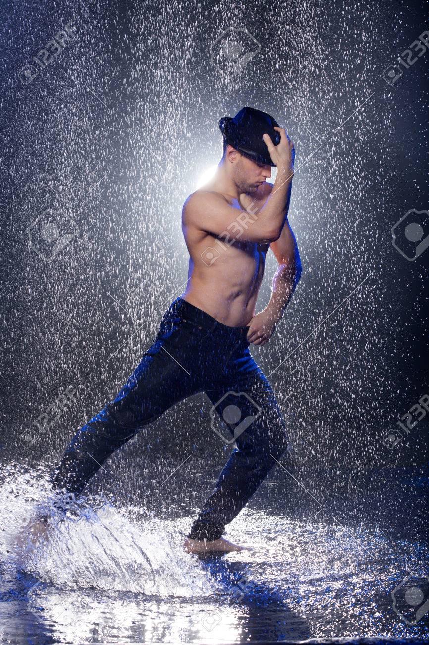 5751cb6df Dancing in the rain. Young male dancer in black fedora dancing..