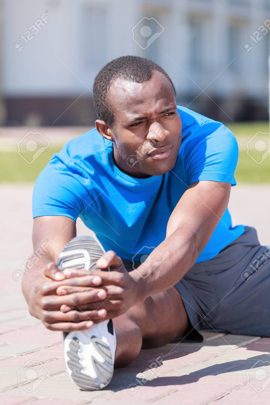 Exercising before jogging. Young african decsent men doing his outdoors exercises Stock Photo - 23926808