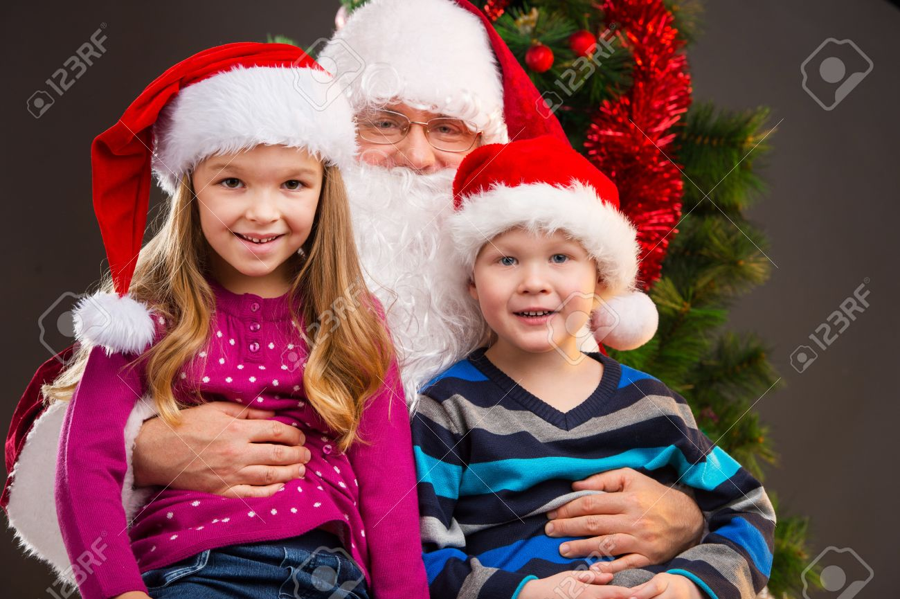 old kind santa claus holding two little kids on his knees smiling and looking at - Santa Claus With Kids