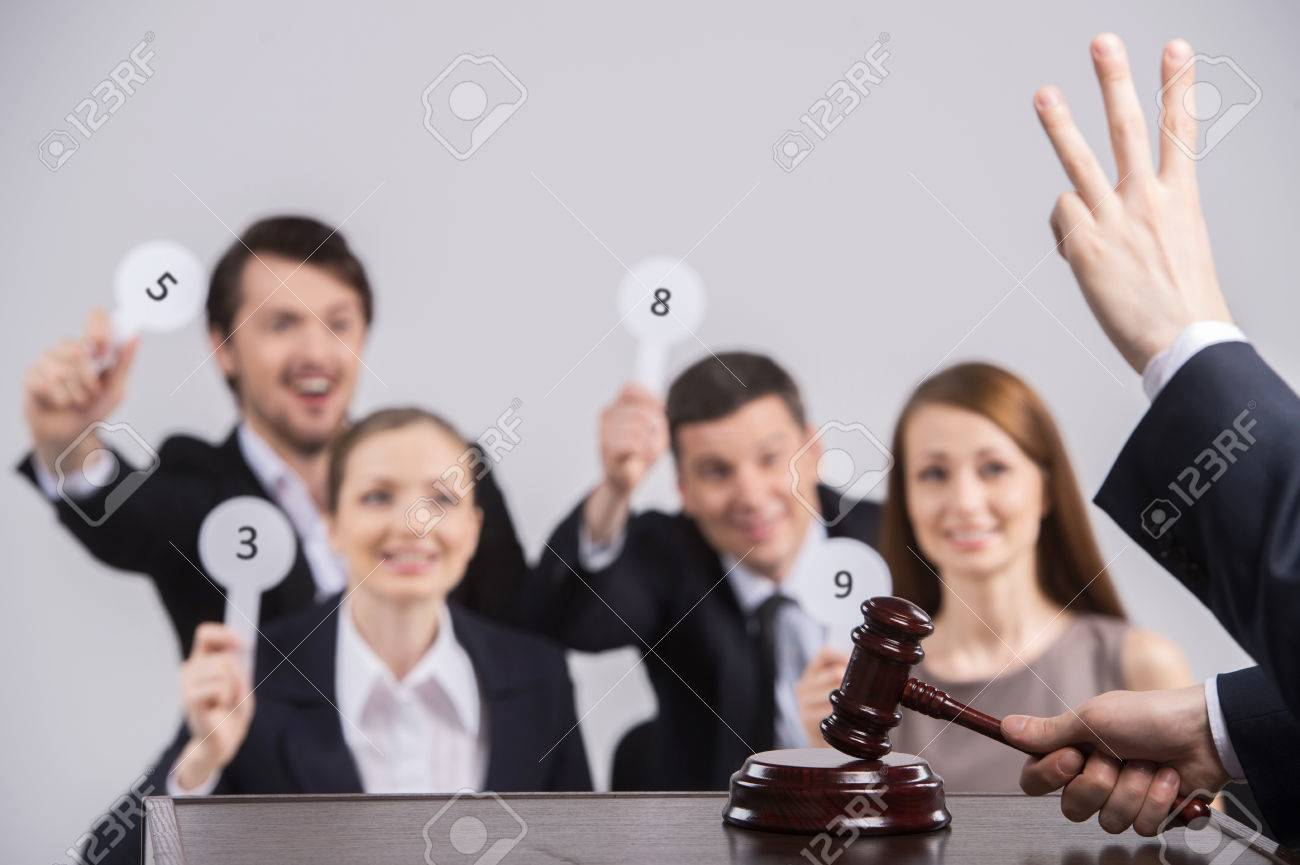 four people raising cards with number. judge counting and holding hammer in hands - 27750383