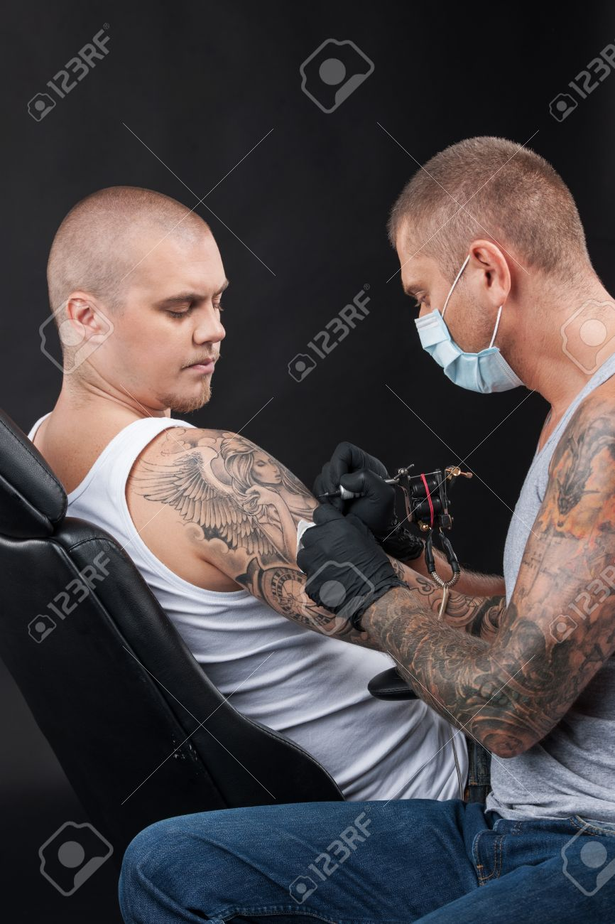 Tatouage Épaule Homme se rapportant à tatoueur professionnel fait tatouage sur l'épaule. homme assis dans