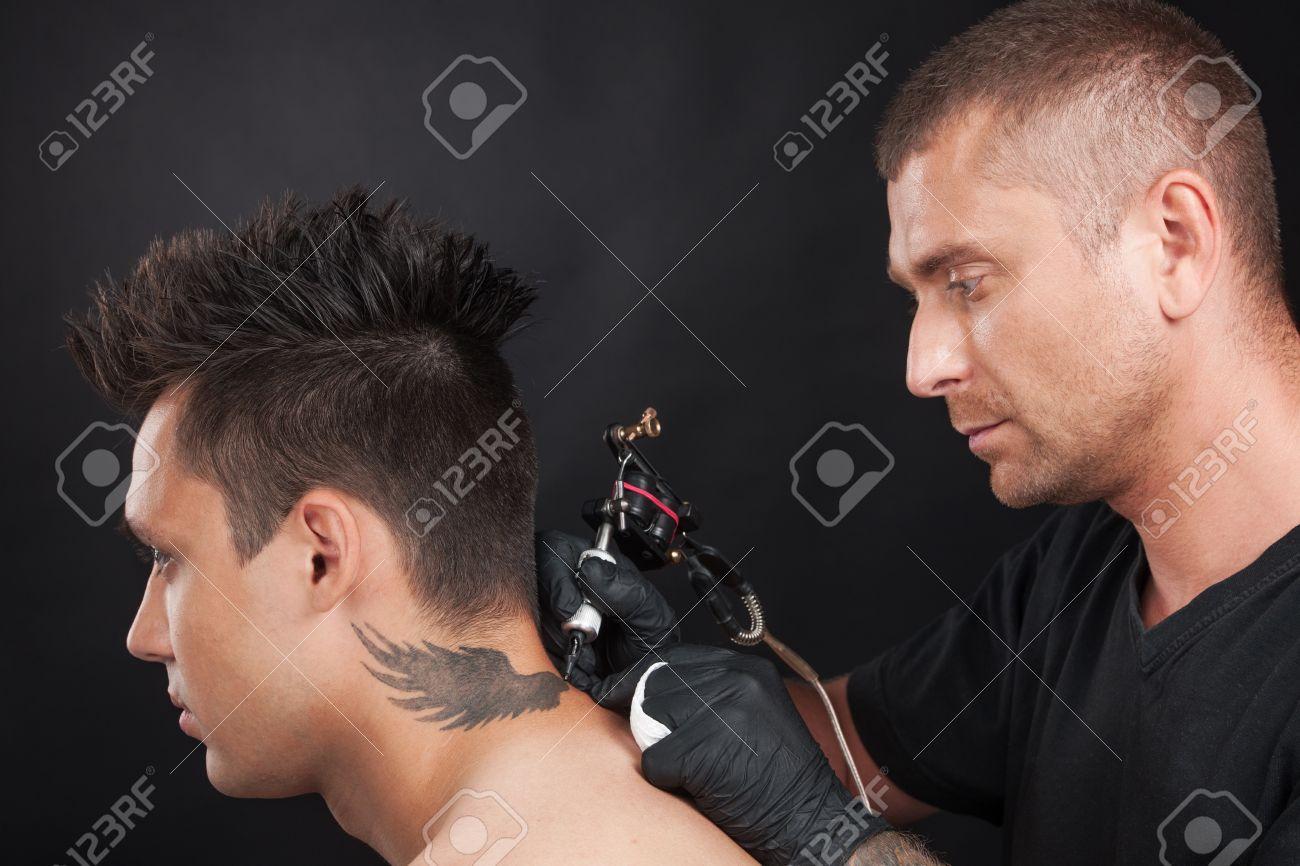 Tatuador Profesional De Dibujo Alas De águila Joven Sentado Con El