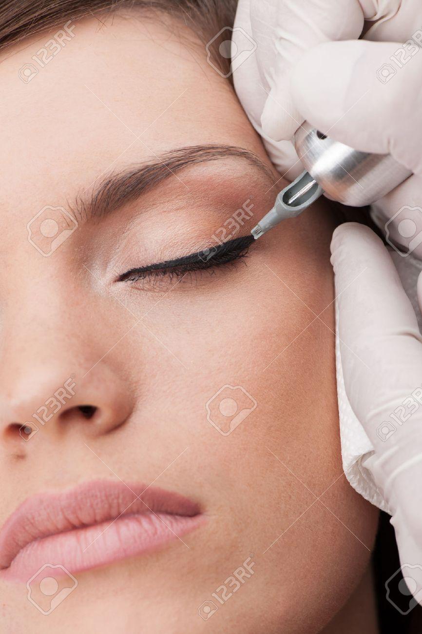 professional tattooist making permanent make-up. beautiful young woman getting tattoo - 27044232