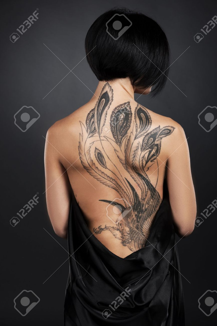 beautiful young lady with back tattoo. dark hair girl with tattoo on black background Stock Photo - 27043496